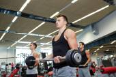 Group of men flexing muscles with barbell in gym — Stock Photo