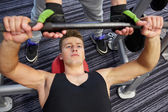 Men doing barbell bench press in gym — Stock Photo