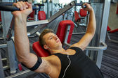 Young man with earphones exercising on gym machine — Stock Photo