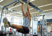 Man flexing abdominal muscles on pull-up bar — Foto de Stock