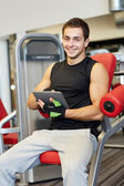 Smiling young man with tablet pc computer in gym — 图库照片