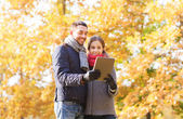 Smiling couple with tablet pc in autumn park — Stock Photo