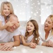 Smiling parents and two little girls at home — Stock Photo #58298529