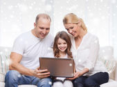 Smiling family with laptop at home — Foto de Stock
