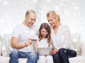 Happy family with tablet pc and credit card — Photo