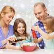 Happy family with two kids making salad at home — Stock Photo #58300141
