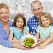 Happy family with two kids showing salad in bowl — Stock Photo #58300361