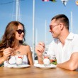 Smiling couple eating dessert at cafe — Stock Photo #58309587