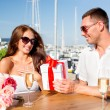 Smiling couple with gift box cafe — Stock Photo #58309625