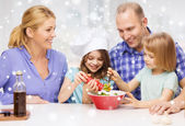 Happy family with two kids making salad at home — ストック写真