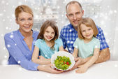 Happy family with two kids showing salad in bowl — ストック写真