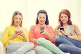 Smiling teenage girls with smartphones at home — Photo
