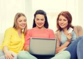 Smiling teenage girls with laptop and credit card — Stock Photo