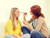 Two smiling teenage girls applying make up at home — ストック写真
