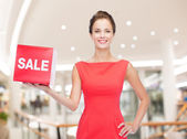 Smiling woman in red dress hat with sale sign — ストック写真