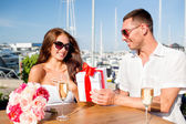 Smiling couple with gift box cafe — Stock Photo