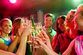 Улыбающиеся друзья с бокалами и пивом в клубе — Стоковое фото
