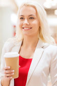 Happy young woman with coffee paper cup in mall — ストック写真