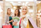 Young women with shopping bags and money in mall — Stock Photo