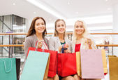 Happy young women with shopping bags in mall — ストック写真