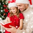 Smiling father and girl in santa hats reading book — Stock Photo #58376363