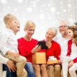 Smiling family with tablet pc and gift box at home — Stock Photo #58378149