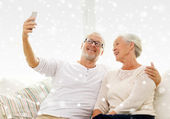 Happy senior couple with smartphone at home — Stock Photo