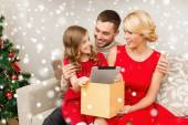 Smiling family taking tablet pc out from gift box — Stock Photo