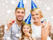 Smiling family in party hats blowing favor horns — Stok fotoğraf