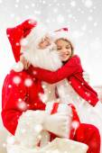 Smiling girl with santa claus and gift at home — Stockfoto