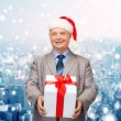 Smiling man in suit and santa helper hat with gift — Stock Photo #58383507