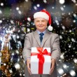 Smiling man in suit and santa helper hat with gift — Stock Photo #58383525