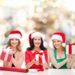 Smiling women in santa helper hats packing gifts — Stock Photo #58383711