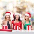 Smiling women in santa helper hats packing gifts — Stock Photo #58383743