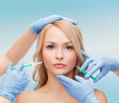 Woman face and beautician hands with syringes — Stock Photo