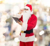 Man in costume of santa claus with tablet pc — Stockfoto