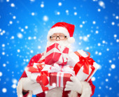 Man in costume of santa claus with gift boxes — Stock Photo
