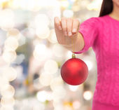 Close up of woman in sweater with christmas ball — Stockfoto