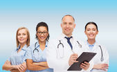 Group of smiling doctors with clipboard — Stock Photo