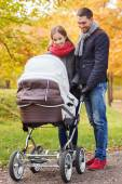 Smiling couple with baby pram in autumn park — Stock Photo