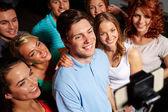 Friends with smartphone taking selfie in club — Foto Stock