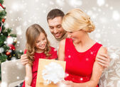 Smiling family looking into open gift box — Stock Photo