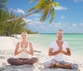 Smiling couple meditating on tropical beach — Stock Photo