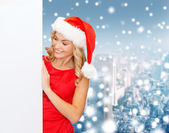 Smiling young woman in santa hat with white board — Stock Photo
