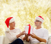 Happy senior couple in santa hats with gift box — Stock Photo