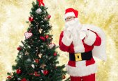 Santa claus with bag and christmas tree — Stock Photo