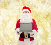 Man in costume of santa claus with laptop — Stock Photo