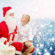 Smiling little boy with santa claus and gifts — Stock Photo #58461331