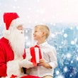 Smiling little boy with santa claus and gifts — Stock Photo #58461521