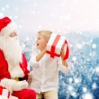 Smiling little boy with santa claus and gifts — Stock Photo #58461567